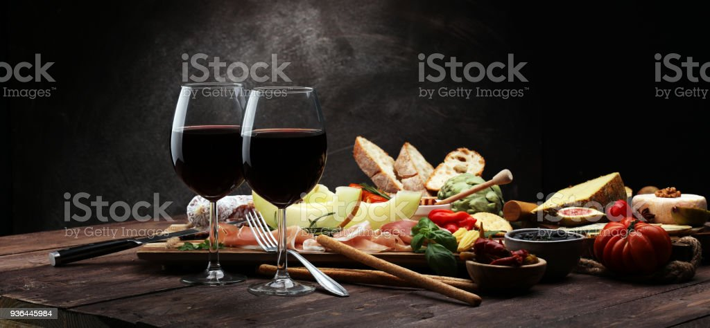 Italian antipasti wine snacks set. Cheese variety, Mediterranean olives, pickles, Prosciutto di Parma with melon, salami. stock photo