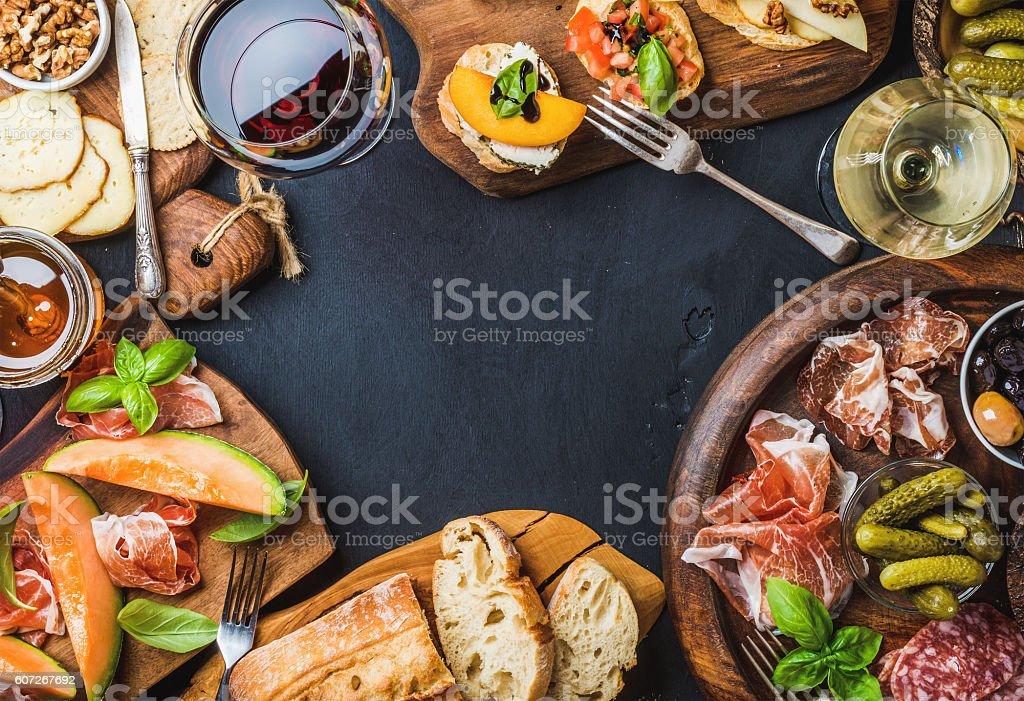Italian antipasti wine snacks set over black grunge background foto