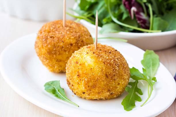 Italian appetizer arancini, rice balls stuffed with meat in oil stock photo