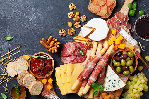 istock Italian appetizers or antipasto set with gourmet food on kitchen table top view. Mixed delicatessen of cheese and meat snacks with red wine. 1148761368