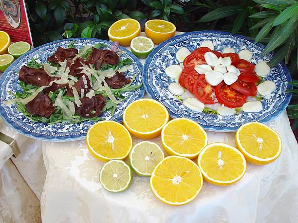 italiano banchetto con insalata caprese e carpaccio - bresaola foto e immagini stock