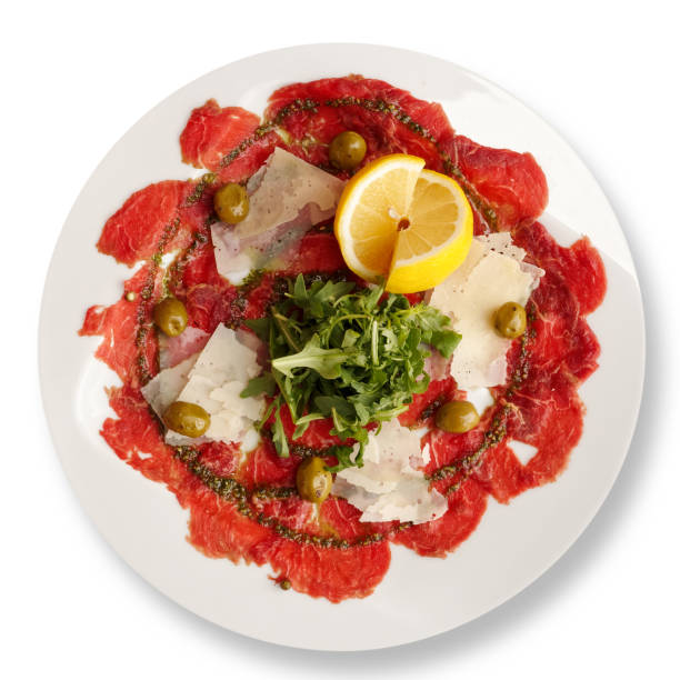 italienische rindercarpaccio mit gehobeltem parmesan und rucola, isoliert auf weiss von oben. - carpaccio salat stock-fotos und bilder