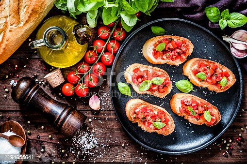 Top view of a homemade Italian bruschetta made with cherry tomatoes, basil, olive oil, garlic and salt disposed on a black plate surrounded by the ingredients for preparing the bruschetta on a dark brown wooden table. Low key DSLR photo taken with Canon EOS 6D Mark II and Canon EF 24-105 mm f/4L