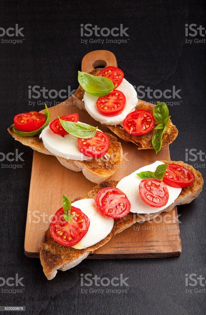 italian bruschetta with cherry tomatoes, mozzarella & fresh basi stock photo