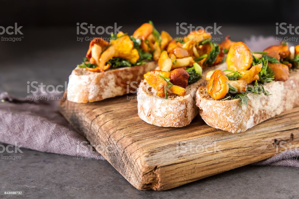 Italian bruschetta with mushrooms chanterelles. Dark wooden background. stock photo
