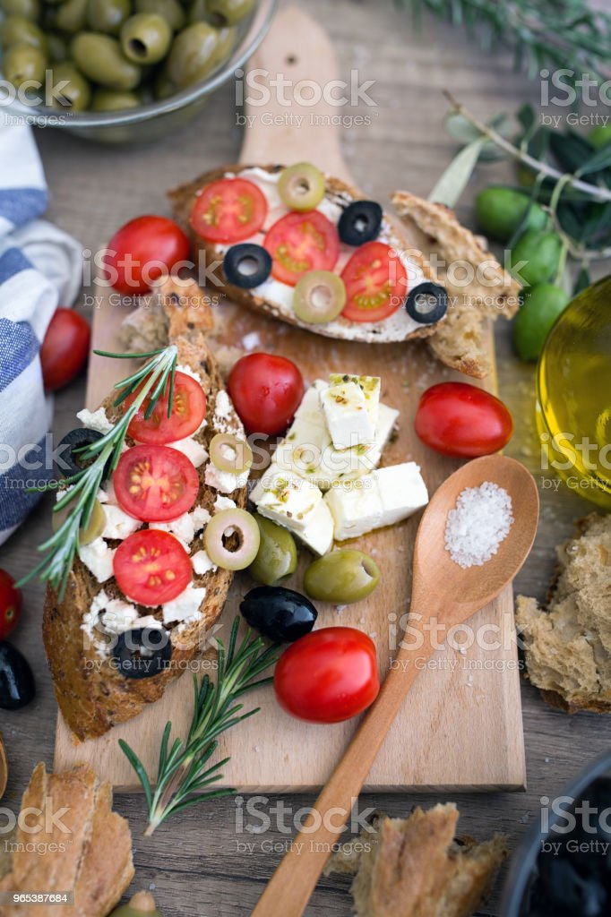 Italian bruschetta with tomatoes, mozzarella cheese, olives and fresh vegetables royalty-free stock photo