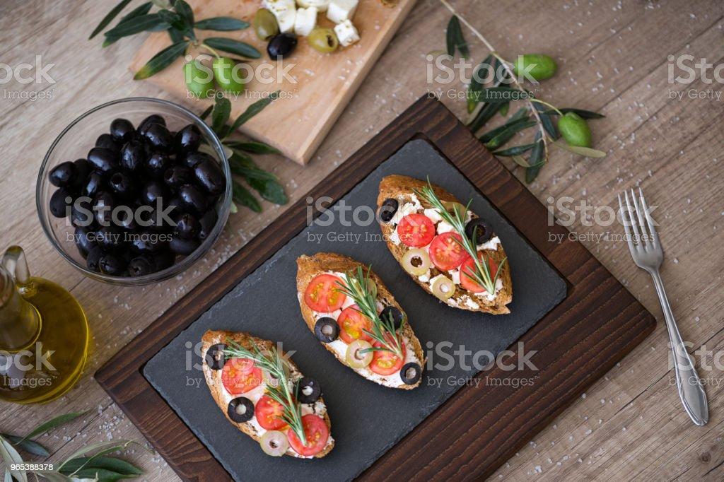 토마토, 모 짜 렐 라 치즈, 올리브와 접시에 신선한 야채와 함께 이탈리아 브루 쉐 타 - 로열티 프리 0명 스톡 사진
