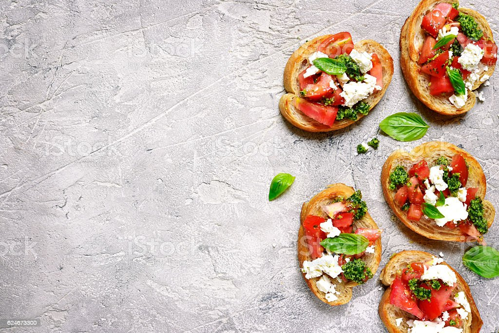 Italian bruschetta with tomatoes,feta and basil pesto on . стоковое фото