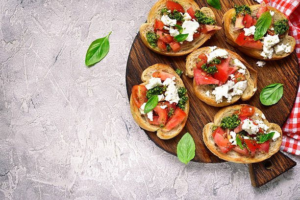 italian bruschetta with tomatoes,feta and basil pesto. - 브루스케타 뉴스 사진 이미지
