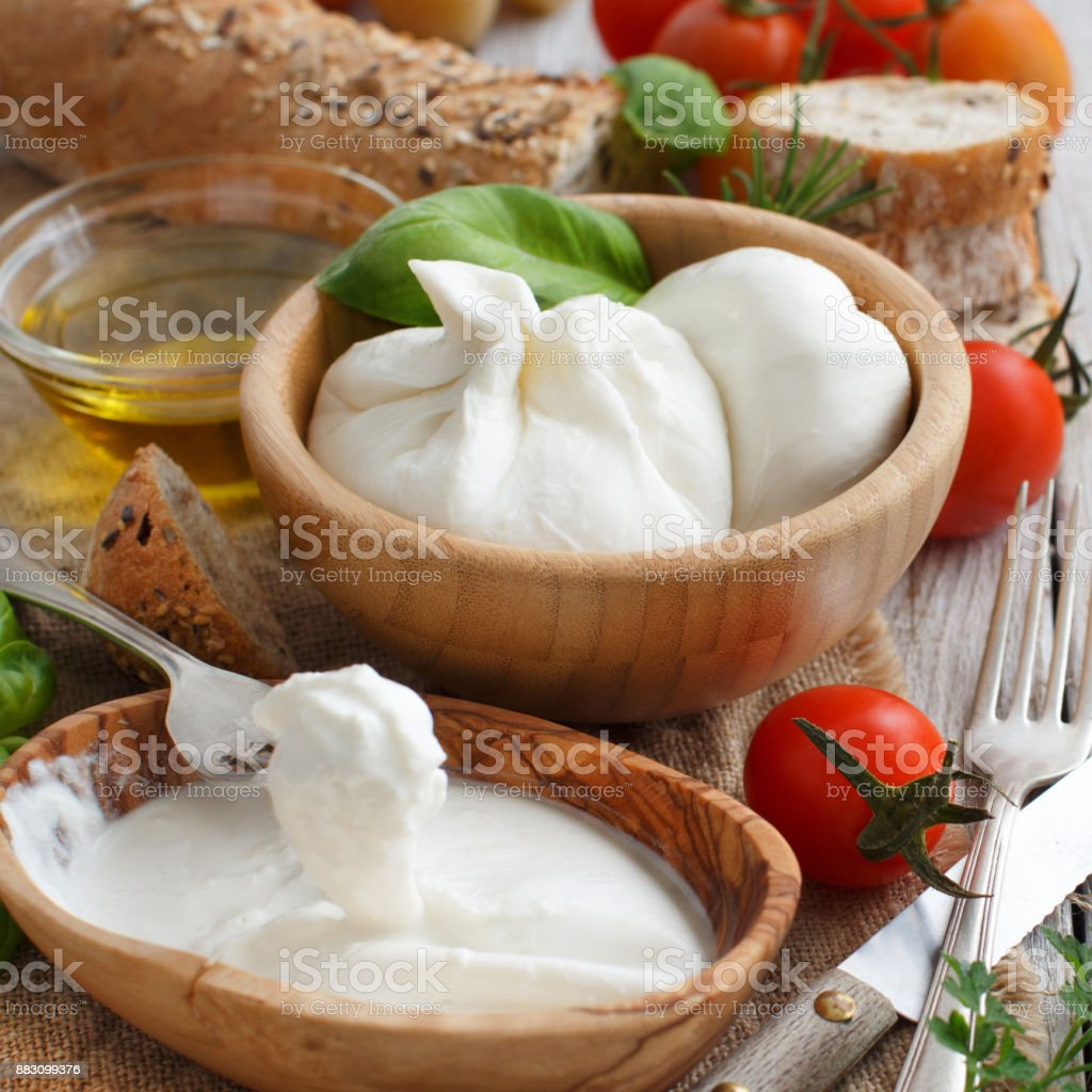 Italian cheese burrata with bread, vegetables and herbs stock photo