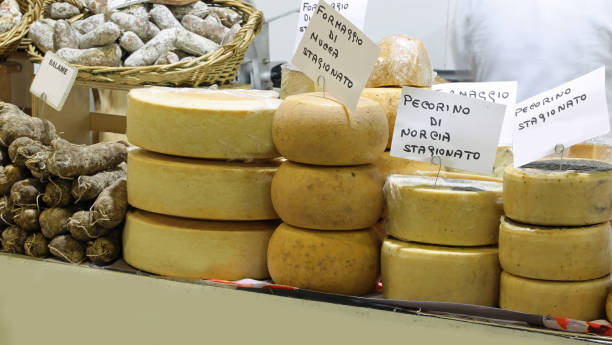 italian cheese with text PECORINO that means cheese made with mi many italian cheese with text PECORINO that means cheese made with milk of sheep and goat in dairy umbria stock pictures, royalty-free photos & images