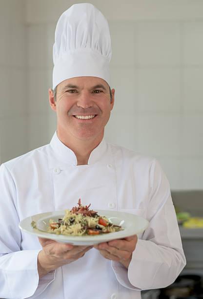 italian chef presenting a plate - italienische küchen dekor stock-fotos und bilder