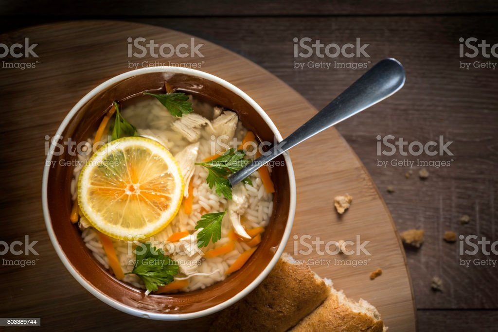 Italian chicken soup with a slice of lemon and with wheat bread on a wooden round table. stock photo