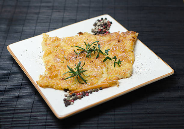Italian chickpea farinata on plate Italian chickpea farinata on white plate, dark background farinata stock pictures, royalty-free photos & images