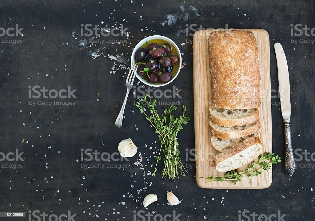 Italian ciabatta bread cut in slices on wooden chopping board stock photo