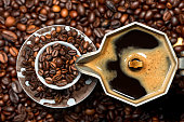 Close-up of an Italian coffee maker and a cup full of roasted coffee beans, top view