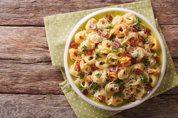 italienisch gefärbt tortellini mit parmesan und in scheiben geschnittene wurst nahaufnahme. horizontale ansicht von oben - käse wurst salat stock-fotos und bilder