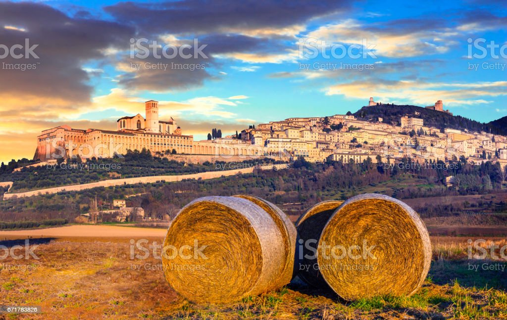 Italian countryside with hey rolls with view of impressive Assisi town on dawn. Umbria stock photo