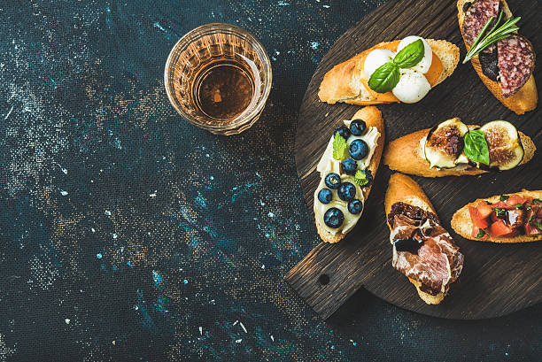 Italian crostini and glass of rose wine over dark background stock photo