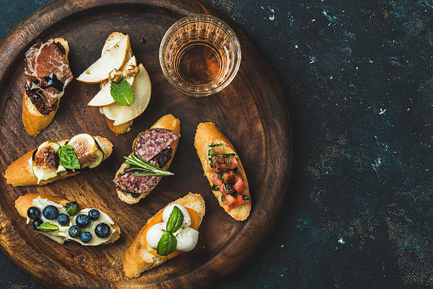 Italian crostini and glass of wine in wooden tray - foto de stock