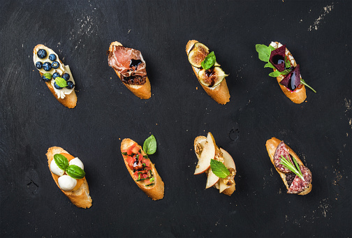 istock Italian crostini with various toppings on black plywood background 590141586