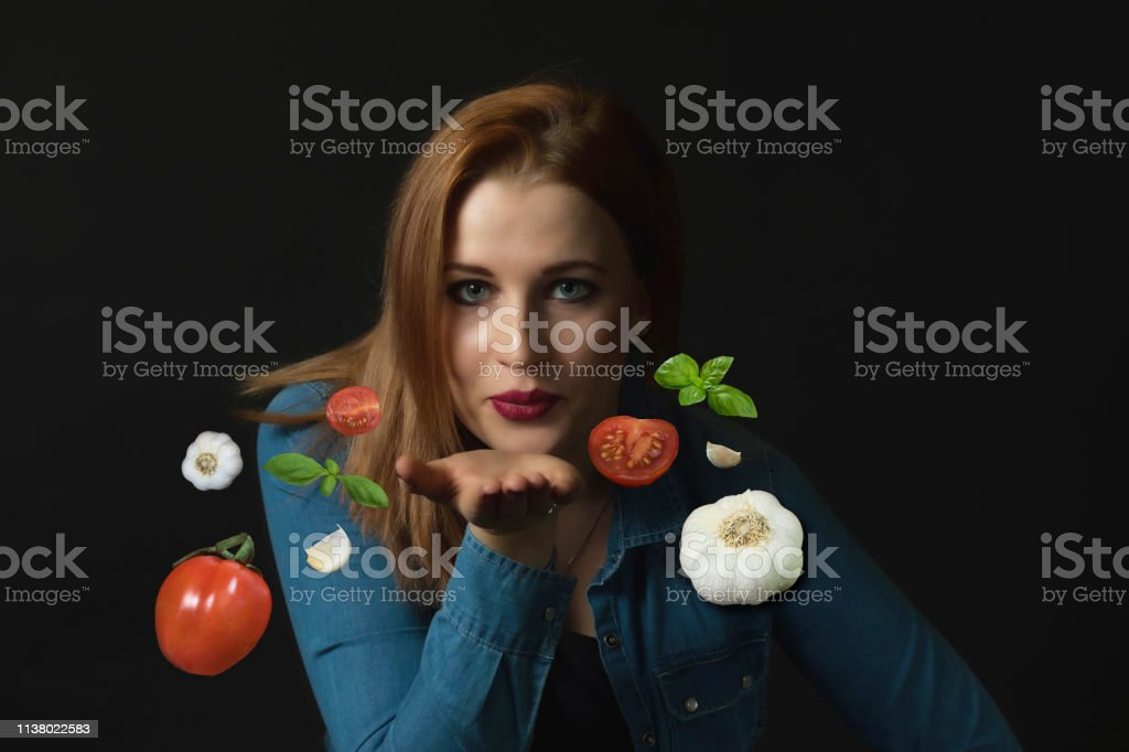 Italian cuisine concept. Young woman sending a kiss with a open palm....