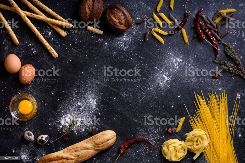 Italian cuisine ingredients - pasta spaghetti on dark background. stock photo