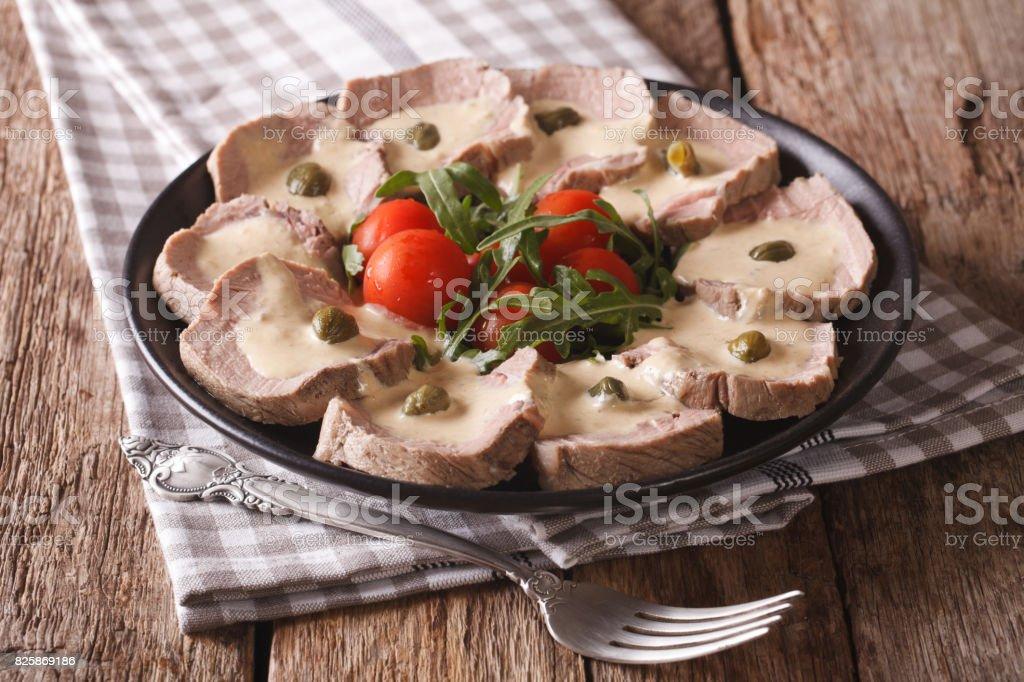 Italian cuisine: Vitello tonnato with capers, arugula, tomatoes close-up. Horizontal stock photo