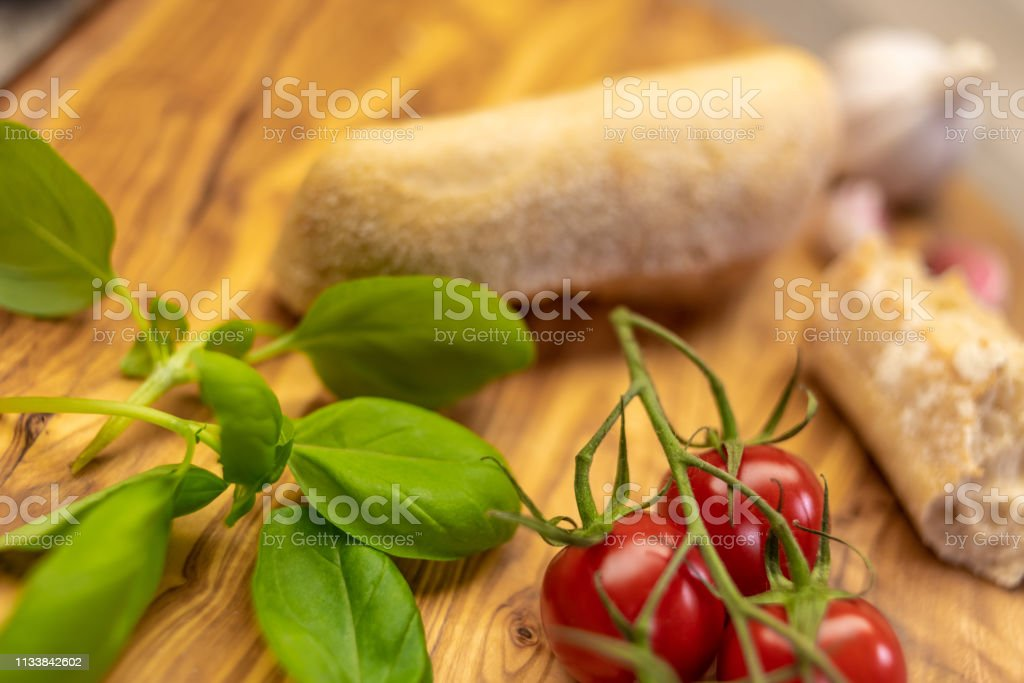 Italian cuisine with cherry tomatoes, olive oil, basil and rustic bread stock photo