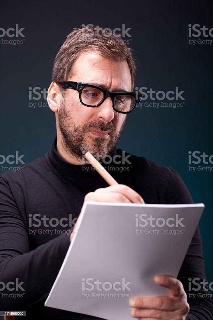 Italian Designer with Retro Eyeglasses Writing on Sketchpad stock photo