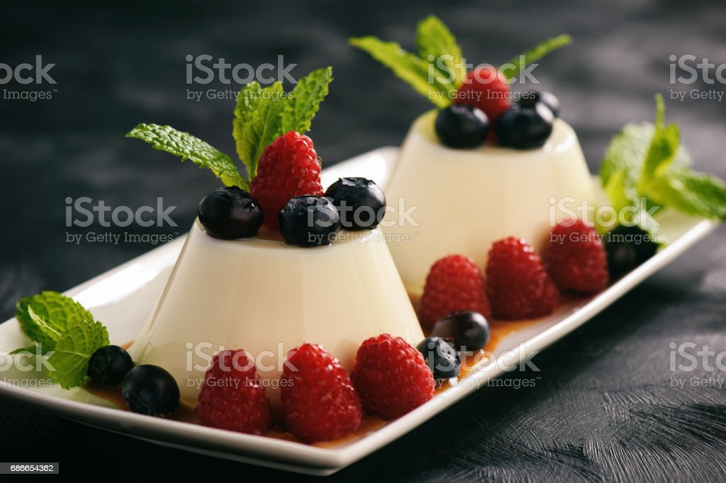Italian dessert - panna cotta with berries and caramel sauce. royalty-free stock photo