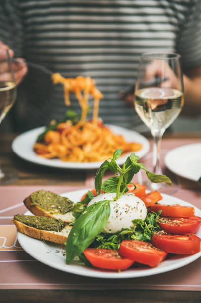 italian dinner at bistrot with caprese and pasta - foodie stock photos and pictures