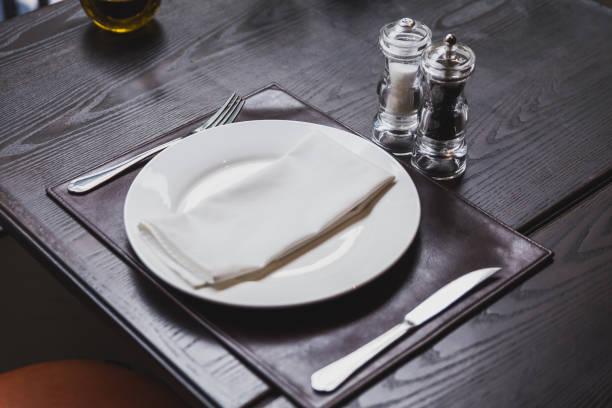 mesa de jantar italiana com talheres, prato, copo, guardanapos e naperies com sal e pimenta na mesa. - fine dining - fotografias e filmes do acervo