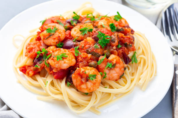 Italian dish shrimp linguine Puttanesca, pasta with shrimps in spicy tomato basil sauce garnished with parsley, horizontal, closeup stock photo