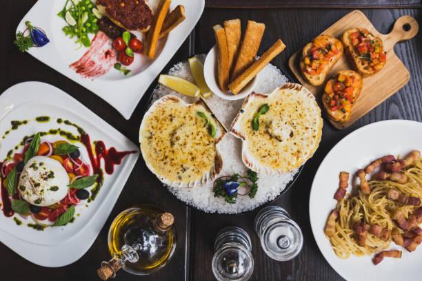 italienische gerichte auf den tisch, einschließlich burrata salat, baked cod mit soße, spaghetti carbonara, gebackene jakobsmuscheln mit käse und kanapees mit olivenöl, pfeffer und salz auf dem tisch. - pasta deli stock-fotos und bilder