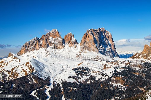 Italian Dolomites Mountains Fassa Valley Sassolungo with the peaks Spallone, Punta Grohmann and Cinque Dita in winter with wonderful sunlight, view from the slope sass Bece