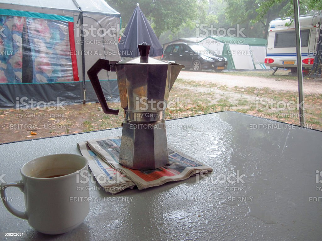 An Espresso machine is standing on a soaking wet camping table while...