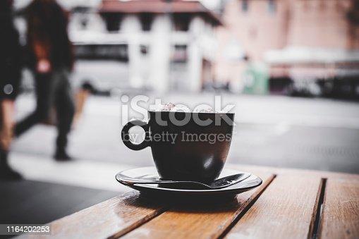 Italian espresson con panna in a black cup. Espresso with whipped cream.