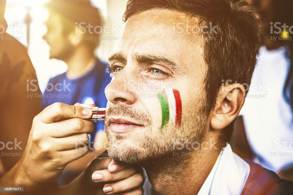 Italian Fan Ready for the Competition, Painting Flag on Cheeks stock photo
