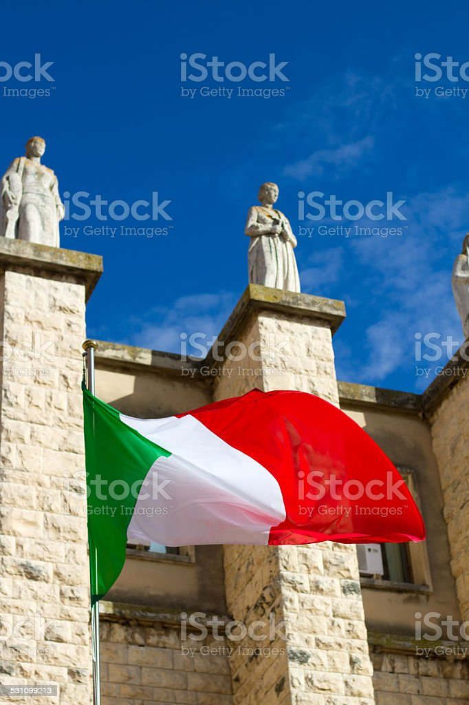 The Italian flag waves in front of the main post office in Ragusa,...