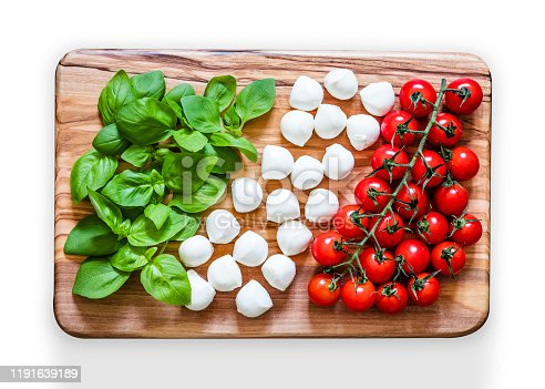Top view of a wooden cutting board with caprese salad ingredients like basil, bocconcini mozzarella cheese and cherry tomatoes making an Italian flag. The cutting board is at the center of the image and is on a isolated on white background. Low key DSLR photo taken with Canon EOS 6D Mark II and Canon EF 24-105 mm f/4L