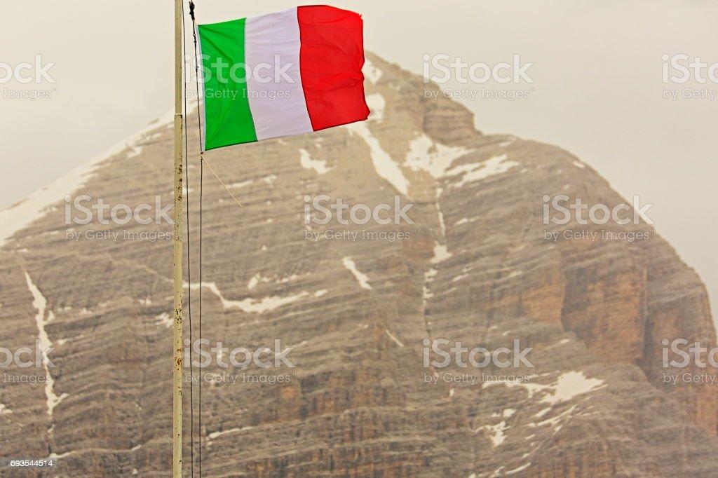 Italian Flag winding above Mount Tofano - Idyllic Lagazuoi summit panorama, Cinque Torri Dolomites, pinnacles mountain range, dramatic and majestic Italy tirol alps stock photo