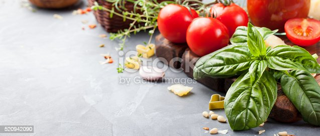 Italian food background with vine tomatoes, basil, spaghetti, olives, parmesan, olive oil, garlic Ingredients on stone table Copy space