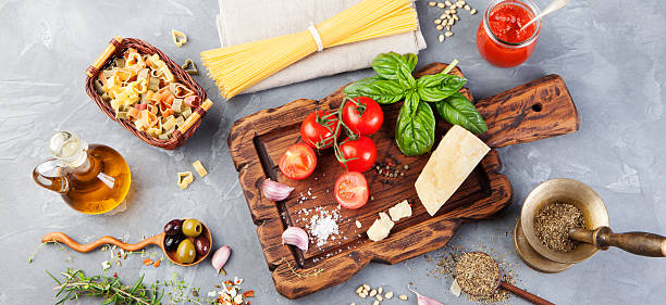 italian food background tomatoes, basil, spaghetti, parmesan, olive oil, garlic - italienische lebensart stock-fotos und bilder