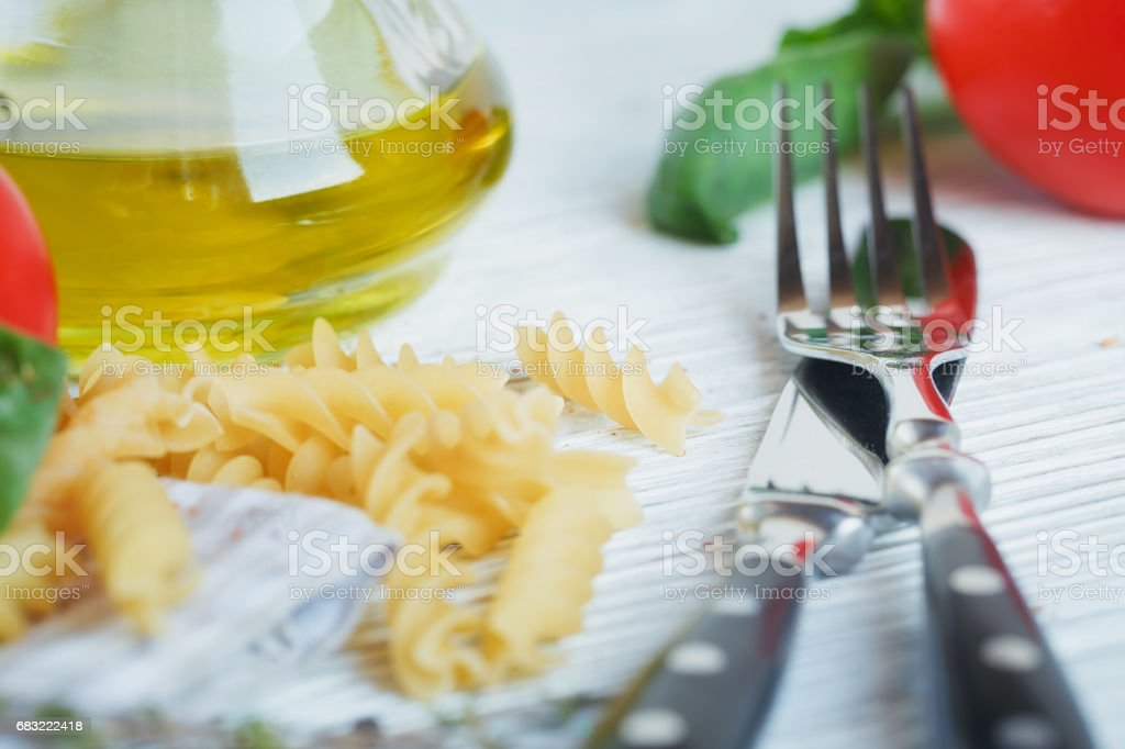 Italian food background with tomatoes, basil, pasta, olive oil, peppercorns, chili pepper and thyme. royalty-free stock photo
