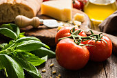 Italian food background with tomatoes on vine, basil, olive oil, parmesan cheese and ciabatta bread. Closeup, selective focus