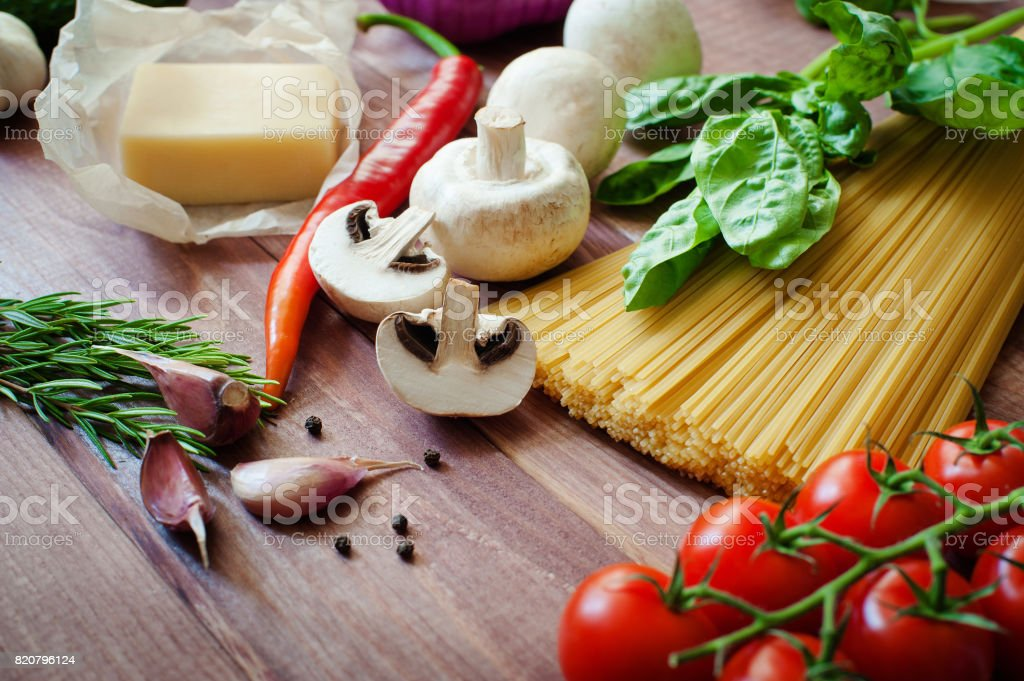 Italian food background, with vine tomatoes, basil, spaghetti, mushrooms, parmesan, garlic, peppercorns, rosemary, parsley and thyme. Wooden background. stock photo