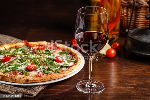 istock Italian food. Classic thin pizza with large sides, prosciutto, cherry tomatoes, arugula, parmesan cheese. Serving dishes in a restaurant on a white plate with red wine. 1202356083