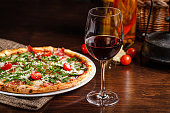 Italian food. Classic thin pizza with large sides, prosciutto, cherry tomatoes, arugula, parmesan cheese. Serving dishes in a restaurant on a white plate with red wine.