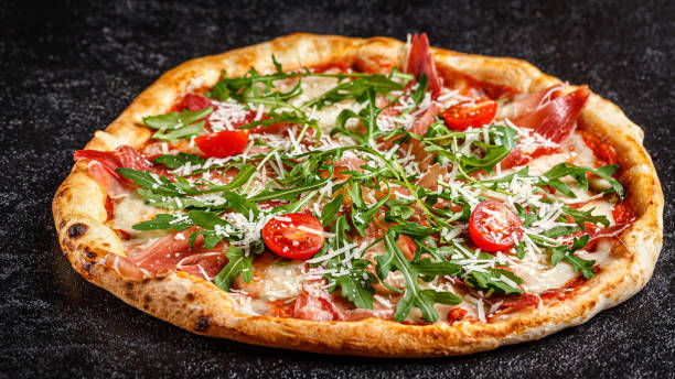Italian food. Classic thin pizza with large sides, prosciutto, cherry tomatoes, arugula, parmesan cheese. Pizza lies on a black background. background image, copy space tex